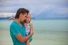 Portret van een klein meisje die met papa op koesteren Stock Foto's