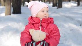 Portret van een klein meisje in een roze jasje en roze hoed in de sneeuw in de winter stock footage
