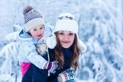 Portret van een klein meisje en haar moeder in de winterhoed in sneeuw F Stock Afbeeldingen