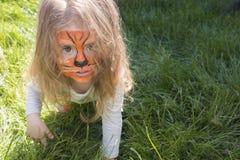Portret van een klein meisje met de make-up van tijgeraqua het kind neemt heimelijk als een tijger Royalty-vrije Stock Afbeelding