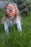Portret van een klein meisje met de make-up van tijgeraqua het kind stelt zich als tijger voor Stock Afbeelding