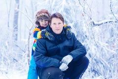 Portret van een kleine jong geitjejongen en zijn jonge vader binnen in sneeuw voor Stock Afbeelding