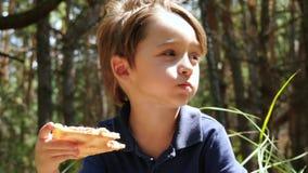 Portret van een kleine jongen De kindbeten van een plak van pizza en eet het Openluchtrecreatie, snack stock video