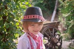 Portret van een kleine jongen in een wit geborduurd overhemd en een hoed stock fotografie
