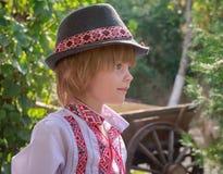 Portret van een kleine jongen in een wit geborduurd overhemd en een hoed stock afbeeldingen