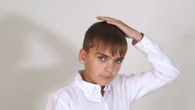 Portret van een kleine jongen in een wit overhemd in de Studio op een witte achtergrond stock video