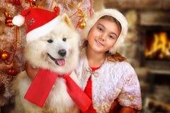 Portret van een kleine meisje en een hond bij Kerstmis Stock Afbeeldingen
