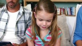 Portret van een kleine meisjeszitting op een bank met haar ouders stock video