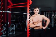 Portret van een knappe atleet bij gymnastiek de mens doet de oefening met barbell, status en het hurken grote zeker Royalty-vrije Stock Foto's