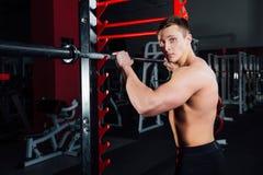 Portret van een knappe atleet bij gymnastiek de mens doet de oefening met barbell, status en het hurken grote zeker Royalty-vrije Stock Foto