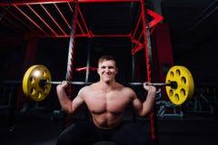 Portret van een knappe atleet bij gymnastiek de mens doet de oefening met barbell, status en het hurken grote zeker Stock Fotografie