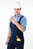Portret van een knappe bouwer die en mobiele telefoon bevinden zich met behulp van Royalty-vrije Stock Afbeelding
