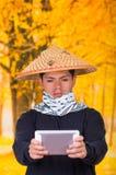 Portret van een knappe ernstige Spaanse jonge bedrijfskerel die een Aziatische kegelhoed dragen die voor hem van hem richten Stock Afbeelding
