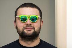 Portret van een knappe jonge gebaarde mens in groene glazen Royalty-vrije Stock Foto