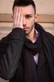 Portret van een knappe jonge mens die een hand op zijn gezicht houden Royalty-vrije Stock Foto's