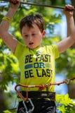 Portret van een knappe jongen op een kabelpark onder bomen De activiteiten van de kinderenzomer royalty-vrije stock fotografie