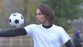 Portret van een knappe kerel in sportent-shirt het spelen met een Gezonde levensstijl van de voetbalbal stock video