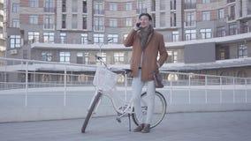 Portret van een knappe mens die op een cel typen terwijl status met een fiets tegen de achtergrond van stedelijke architectuur stock videobeelden