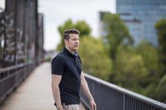 Portret van een Knappe Mens die op een Stadsbrug lopen Stock Foto's