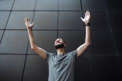 Portret van een knappe modieuze kerel die omhoog met zijn omhoog handen kijken, royalty-vrije stock fotografie