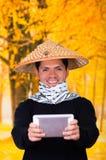 Portret van een knappe Spaanse jonge bedrijfskerel die een Aziatische kegelhoed dragen die voor hem zijn Ipad-het gebruiken richt Stock Fotografie