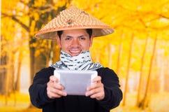 Portret van een knappe Spaanse jonge bedrijfskerel die een Aziatische kegelhoed dragen die voor hem zijn Ipad-het gebruiken richt Stock Afbeelding