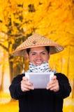 Portret van een knappe Spaanse jonge bedrijfskerel die een Aziatische kegelhoed dragen die voor hem zijn Ipad-het gebruiken richt Royalty-vrije Stock Afbeelding
