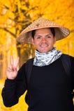 Portret van een knappe Spaanse jonge bedrijfskerel die een Aziatische kegelhoed dragen en een overwinningssignaal in autum doen Royalty-vrije Stock Afbeelding