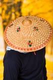 Portret van een knappe Spaanse jonge bedrijfskerel die een Aziatische kegelhoed dragen en zijn gezicht met de hoed verbergen, bin Stock Foto's