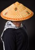 Portret van een knappe Spaanse jonge bedrijfskerel die een Aziatische kegelhoed dragen en zijn gezicht met de hoed verbergen, bin Royalty-vrije Stock Fotografie