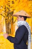 Portret van een knappe Spaanse jonge bedrijfskerel die een Aziatische kegelhoed en een sjaal dragen rond zijn halsholding van hem Stock Afbeelding