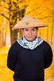 Portret van een knappe Spaanse jonge bedrijfskerel die een Aziatische kegelhoed met wapens in zijn rug in autum dragen Stock Afbeelding