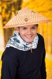 Portret van een knappe Spaanse jonge bedrijfskerel die een Aziatische kegelhoed op autumachtergrond dragen Stock Fotografie