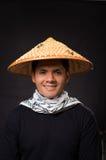 Portret van een knappe Spaanse jonge bedrijfskerel die een Aziatische kegelhoed op zwarte achtergrond dragen Royalty-vrije Stock Afbeeldingen