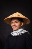 Portret van een knappe Spaanse jonge bedrijfskerel die een Aziatische kegelhoed op zwarte achtergrond dragen Stock Foto