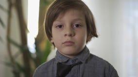 Portret van een knappe succesvolle kleine jongen die een band binden Kinderen als volwassenen Volwassen kind stock video