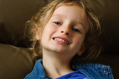 Portret van een krullend blauw-eyed meisje met een zekere glimlach Zij toont haar witte melktanden Royalty-vrije Stock Foto's
