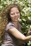Portret van een krullend meisje dichtbij jasmijnbloemen Stock Foto's