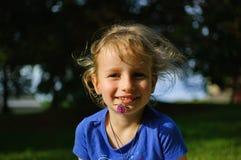 Portret van een krullend meisje met blond haar op het gras Zij houdt een violette klaverbloem in haar mond De baby glimlacht zo Stock Fotografie