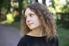 Portret van een krullend meisje in een zwarte kleding in openlucht Royalty-vrije Stock Afbeeldingen