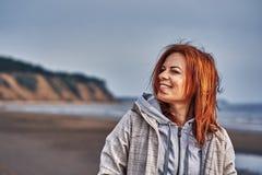 Portret van een lachende vrouw die op middelbare leeftijd met rood haar langs de rivierbank lopen Zonnige de lenteochtend stock afbeeldingen