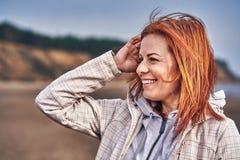 Portret van een lachende vrouw die op middelbare leeftijd met rood haar langs de rivierbank lopen Zonnige de lenteochtend royalty-vrije stock fotografie