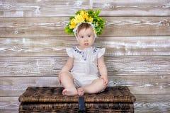 Portret van een leuk babymeisje op een lichte achtergrond met een kroon van bloemen op haar hoofdzitting op bankmand Stock Afbeelding