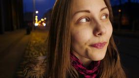 Portret van een leuk glimlachend tienermeisje op een straat van de nachtstad Het lachen en het hebben van pret stock videobeelden