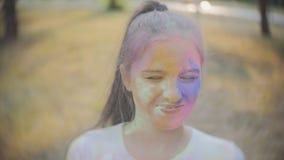 Portret van een leuk meisje dat in de kleuren van Holi-festival wordt geschilderd stock videobeelden