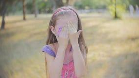 Portret van een leuk meisje dat in de kleuren van Holi-festival wordt geschilderd stock video
