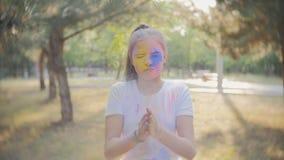 Portret van een leuk meisje dat in de kleuren van Holi-festival wordt geschilderd stock footage
