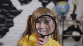 Portret van een leuk meisje dat het speel kijken in vergrootglas Close-up Een mooi meisje onderzoekt camera en glimlacht stock footage