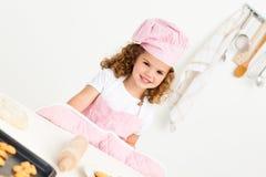 Portret van een leuk meisje dat koekjes voorbereidt stock afbeeldingen