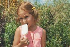 Portret van een leuk meisje met roomijs op een gang in het park Kind in openlucht stock fotografie